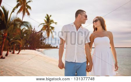 love, travel, summer holidays, people and relations concept - happy couple wearing sunglasses holding hands over exotic tropical beach with palm trees background