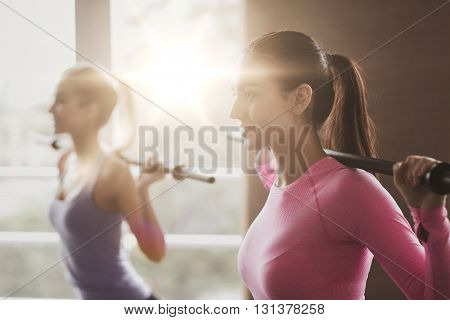 fitness, sport, training, gym and lifestyle concept - group of people exercising with bars in gym