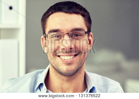business, people and work concept - portrait of  smiling businessman in eyeglasses in office