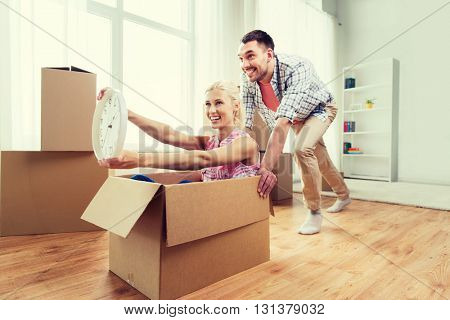 home, people, moving, time and real estate concept - happy couple having fun and riding in cardboard boxes with clock at new home