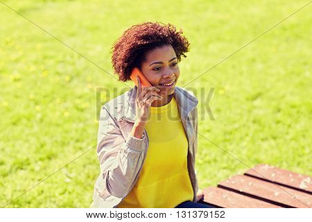 technology, communication and people concept - smiling african american young woman or teenage girl calling on smartphone outdoors