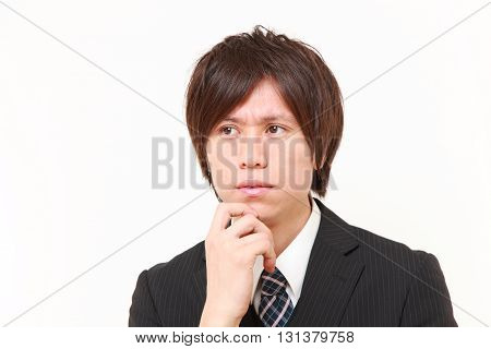 studio shot of  young Japanese businessman worries about something on white background