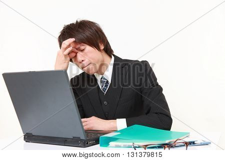 studio shot of young Japanese businessman suffers from Asthenopia on white background