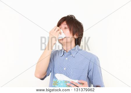 studio shot of young man with a allergy sneezing into tissue on white background