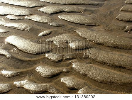 Texture of beach sand ripples with sun light at low tide