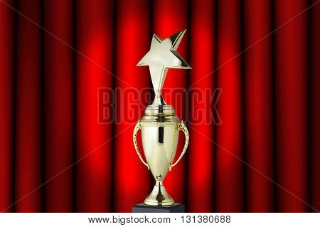 Golden trophy cup on red curtain background