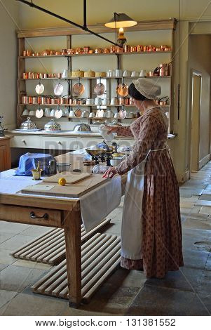 Saffron Walden, Essex, England - May 07, 2016: Victorian Kitchen maid - Cook preparing food .in authentic Victorian kitchen.