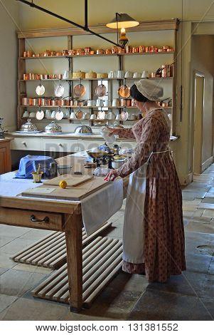 Saffron Walden, Essex, England - May 07, 2016: Victorian Kitchen maid - Cook preparing food .in authentic Victorian kitchen.