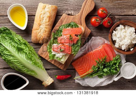 Sandwich with ciabatta bread, salmon, cheese and romaine salad on wooden table. Top view