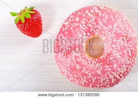 Donut with Strawberry Icing with fresh strawberries on the old wooden table close-up top view