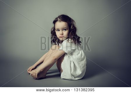 Portrait of cute emotional little girl posing in studio over gray background.