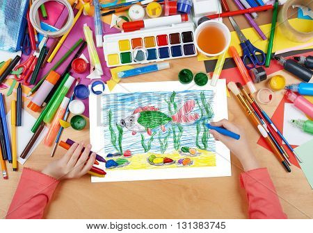 big fish under water child drawing, top view hands with pencil painting picture on paper, artwork workplace