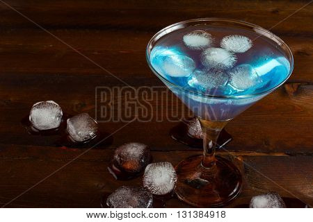 Iced blue cocktail on wooden background. Blue margarita. Blue cosmopolitan. Blue Lagoon. Blue cocktail. Blue Martini. Blue Hawaiian cocktail. Blue curacao liqueur.