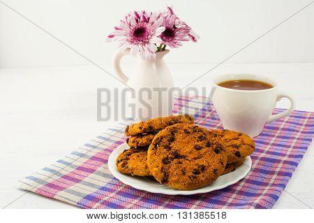 Tea and cookies served on checkered napkin. Homemade biscuit. Homemade cookies.Sweet dessert. Breakfast cookies. Sweet pastry. Cup of tea. Tea cup. Breakfast tea.