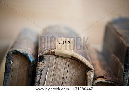 Quiz concept text and old vintage books on a shelf