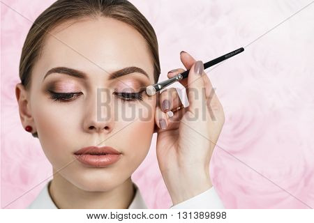 Make-up artist applying bright eyeshadow on model's eye over roses pattern background