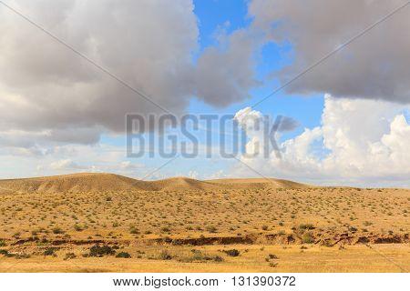 Hills In Desert Under Clouds In Blue Sky