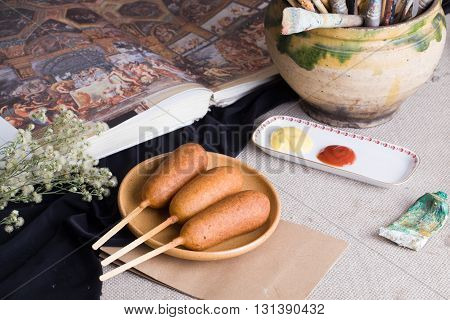 corndog sausage on a stick with mustard ketchup and parsley