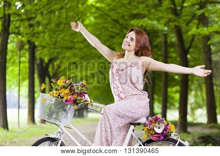 Happy smiling woman on bicycle with arms raised