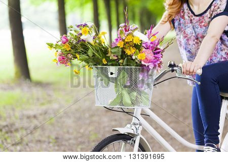 Woman holding a vintage bicycle with flowers in basket at the park