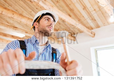 Close-up portrait of a concentratedbuilder with a hammer in his hands at the working area