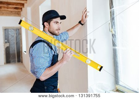 Concentrated young repairman standing with a level in his hands and watching at the window