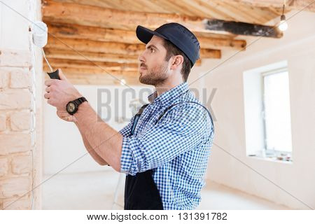 Handsome young builder working with a paint roller indoors