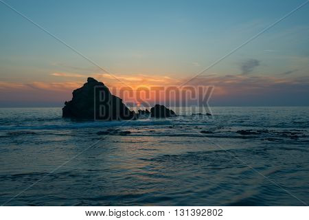 Sunset on the sea shore. The sun sets in the sea against the backdrop of a colorful sky. Waves splashing near the lone rock. Akamas Peninsula. Perspective.
