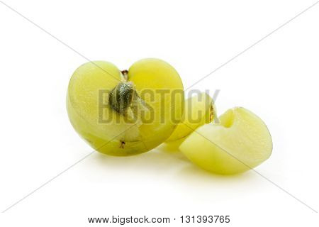 One half and slices of Organic Indian gooseberry or Amla (Phyllanthus emblica) with visible seed isolated on white background.