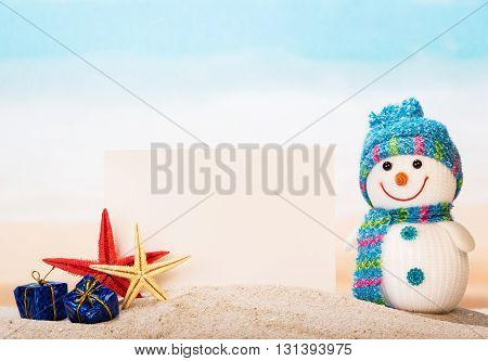 Blank greeting card, starfish, snowman and gifts in the sand of the sea.