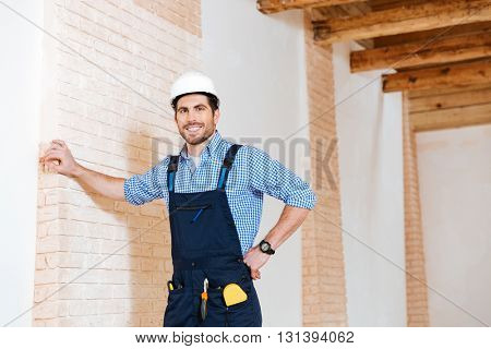 Joyful young builder smiling while standing indoors