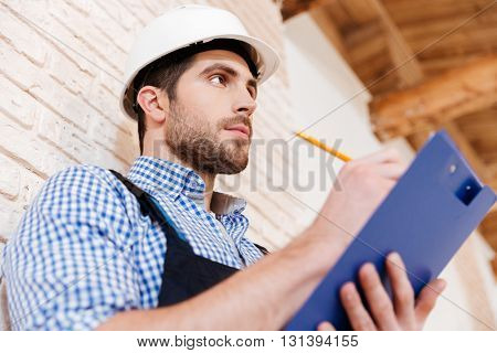 Close-up portrait of a smart pensive builder thinking about something indoors