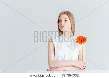 Charming woman sitting at the table and holding flower isolated on a white background