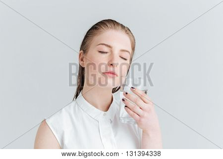 Beauty portrait of a young woman with closed eyes holding glass of water isolated on a white background