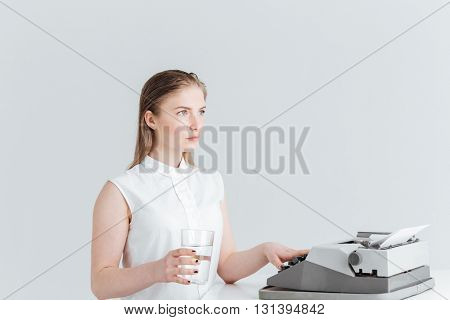 Young woman worrking on retro print machine and holding glass with water isolated on a white background