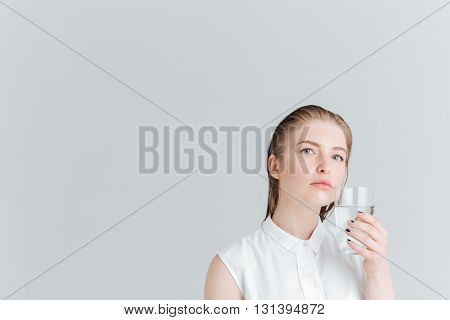 Beauty portrait of a pensive woman holding glass of water isolated on a white background