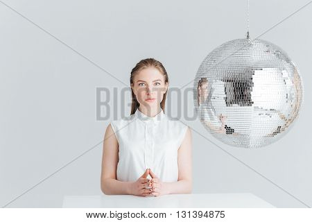 Attractive woman sitting at the table near mirror ball and looking at camera isolated on a white background