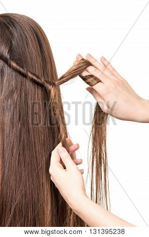 Hairdresser braids long straight brown hair isolated on white background.