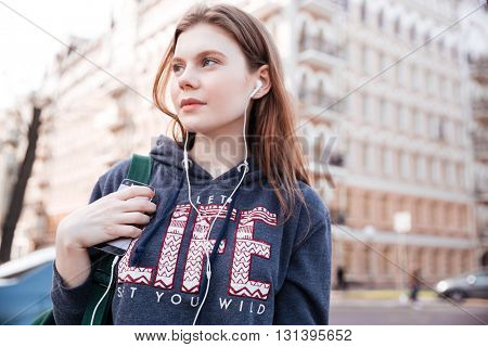 Closeup of thoughtful pretty young woman with backpack listening to music from mobile phone on the street