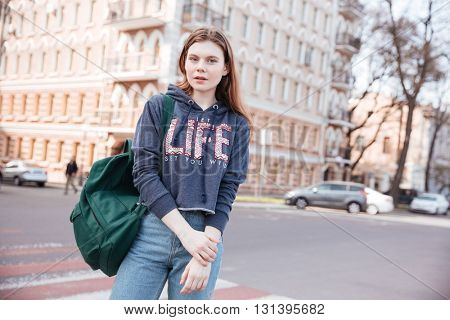Portrait of beautiful young woman with backpack standing near the road in the city