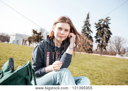 Charming young woman in earphones listening to music on the lawn