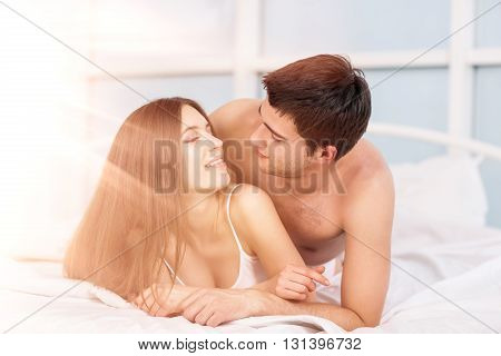 Young love couple in bed, romantic scene in bedroom. Bright daylight shining from the window