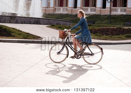 Happy lovely young woman smiling and riding a bike in the city