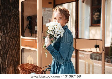 Cute lovely young woman with bicycle and bouquet of camomiles standing near telephone box on the street