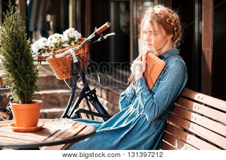 Thoughtful cute young woman with bicycle readng book and dreaming on the beanch outdoors
