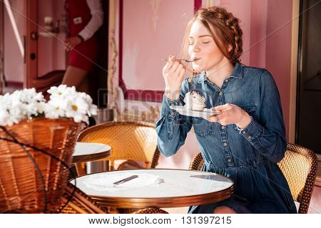 Relaxed pretty young woman sitting and eating cupcake in outdoor cafe