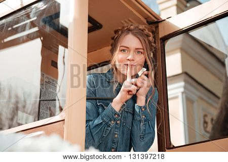 Happy playful young woman calling from telephone box and showing silence sign