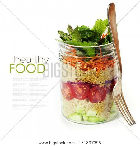 Cucumber, quinoa, tomato, onion, carrot and mint salad in a jar over white