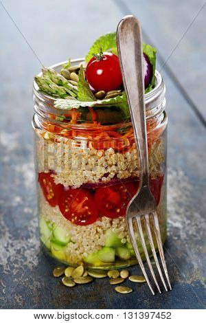 Cucumber, quinoa, tomato, onion, carrot and mint salad in a jar  on rustic wooden table