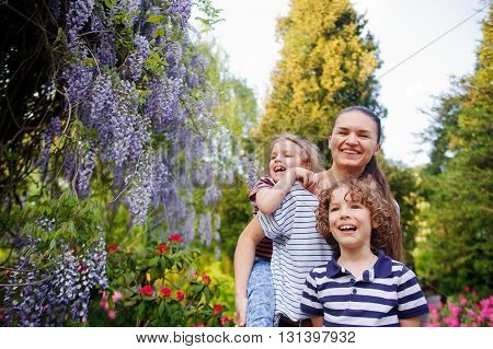 Mother with daughter and son walking in the summer park. Active outdoor recreation. Young woman and her two children came to the park. Cheerful walk in nature. Good mood. Strengthening Family Health